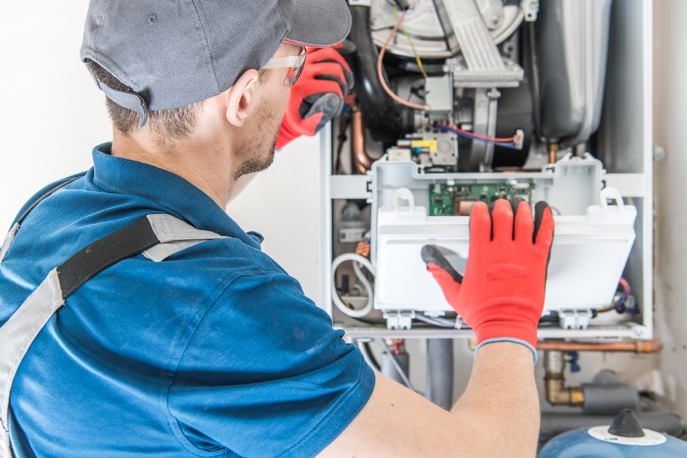 service hvac tech repairing furnace in home