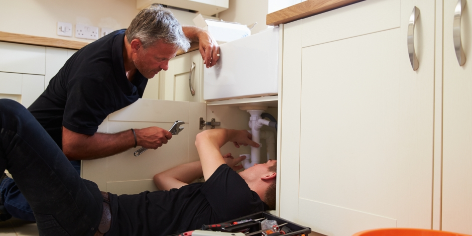 trainee plumber working under sink