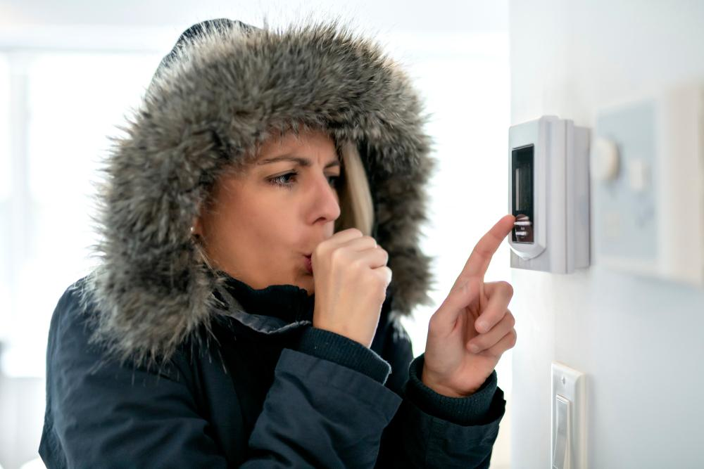 very cold woman at home trying to adjust the thermostat